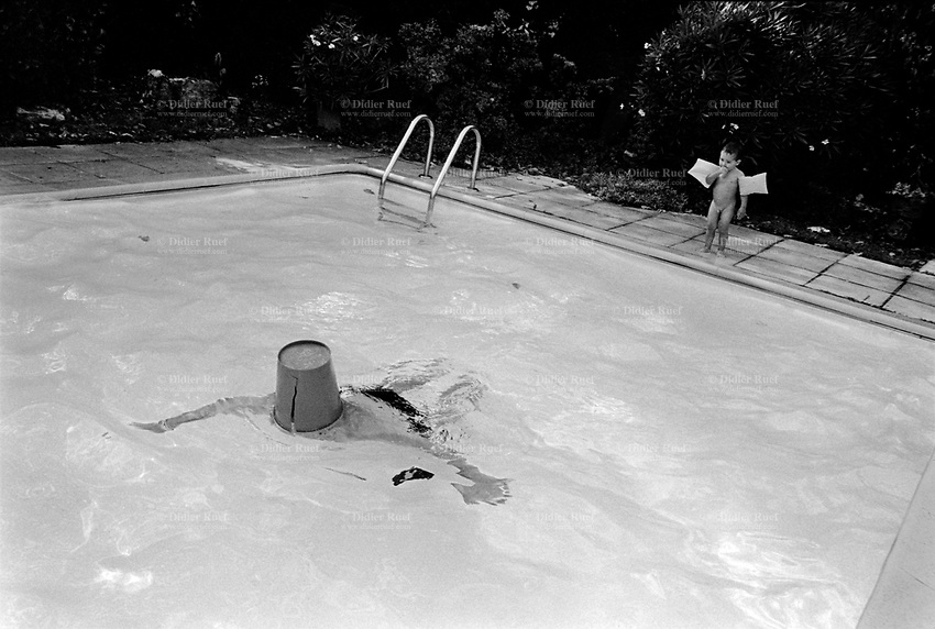France. Alpes-Maritimes Department. Mouans-Sartoux.  Enrico Gastaldello and his son Matteo take a bath in a swimming pool on a hot summer day. The father is swimming breast stroke and his face is covered with a bucket. The naked boy stands on pool's edge and wears inflatable rings on both arms.  © 1999 Didier Ruef