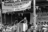 Black activist Angela Davis addresses a rally in the national stadium on International Women's Day.  Prime Minister Maurice Bishop and Finance Minister Bernard Coard are seated on the right.