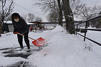 SNOW ROUND 2<br />Gloria Sommers (left) and her husband, Ron, both 80, shovel their driveway on Wednesday Feb. 17 2021  in the Larue community on Beaver Lake in east Benton County after another round of snow. The couple planned to spread play sand mixed with epsom salt on the drive after shoveling. The Sommers measured about 4 inches of snow at their home. Go to nwaonline.com/210218Daily/ to see more photos.<br />(NWA Democrat-Gazette/Flip Putthoff)