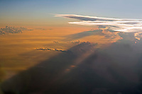 High cloud layers create rays of sunlight in hazy atmoshere, with sunset color