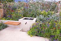 Mixing garden styles: Water garden feature fountain bubbler in silver and blue color theme garden, patio, floating bench, lush flowering perennial bed: Achillea, Astelia, fence, for sleek sophistical style mixed with romantic cottage style