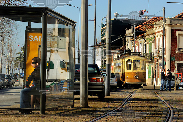 Passengers wait at a bus stop in Porto. Behind runs one of Porto's historic trams, part of a recently restored network of three lines, which were put back into action after the introduction of a modern metro system.