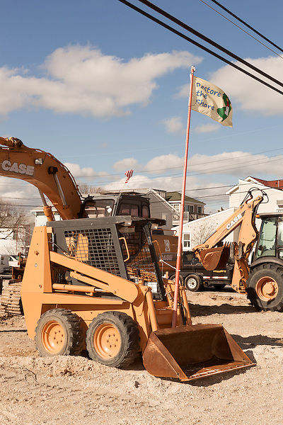 """February 27, 2013. Holgate, New Jersey. A front loader used to dismantle destroyed homes flies the """"Restore the Shore"""" flag in a trailer park that has no livable residences after Hurricane Sandy hit the area.. Tracing the path of Hurricane Sandy, which wrecked havoc on the northeastern seaboard from October 25-31, 2012. The storm caused flooding and caused an estimated 60 billion dollars worth of damage to affected areas."""