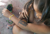 Aldeia Baú, Para State, Brazil. Kayapo girl painting her arm with genipapo dye.
