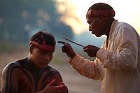 """Lutadores de diversas aldeias se preparam para o Huka-huka.<br /> <br /> Huka-hukaLuta corporal que na terminologia kamaiur· lembra os gritos dos lutadores ao se defrontarem imitando o rugido da onÁa. Os anfitriıes enfrentam uma aldeia convidada de cada vez, comeÁando por lutas individuais de campeıes reconhecidos. Seguem-se lutas simult'neas de v·rios pares de rivais, atÈ as lutas dos muito jovens. Os lutadores se defrontam batendo o pÈ direito no ch""""o, dando voltas no sentido dos ponteiros do relÛgio, com o braÁo esquerdo estendido e o direito retraÌdo, enquanto gritam alternadamente: hu! ha! hu! ha! AtÈ que chocam as m""""os direitas e enlaÁam o pescoÁo do advers·rio com a esquerda. A luta, que pode durar poucos segundos, termina quando um dos advers·rios È derrubado, o que n""""o tem que ocorrer literalmente, bastando que a parte posterior de um de seus joelhos seja agarrada pela m""""o do outro, o que È considerado condiÁ""""o suficiente para provocar-lhe a queda. As aldeias convidadas n""""o lutam entre si. Os enfeites dos troncos do Kwarup podem ser dados aos lutadores vencedores e tambÈm aos dois tocadores de marac·..<br /> QuerÍncia, Mato Grosso, Brasil. <br /> Foto Paulo Santos<br /> 26/07/2015<br /> <br /> Fonte: ISA"""