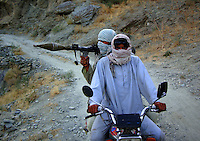 Two foot soldiers from the Wardak Mobile Patrol Unit patrol their area by chinese motorcycle armed with a RPG [rocket propelled grenade]