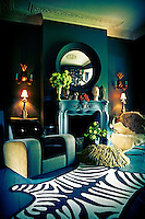 A traditional room decorated in shades of blue with a large circular mirror above the fireplace. The sitting room is furnished with an eclectic mix of seating and a zebra pattern rug on a painted floor.