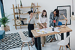 K46HHM Multiethnic group of young businesswomen working with blueprint and drinking coffee in modern office