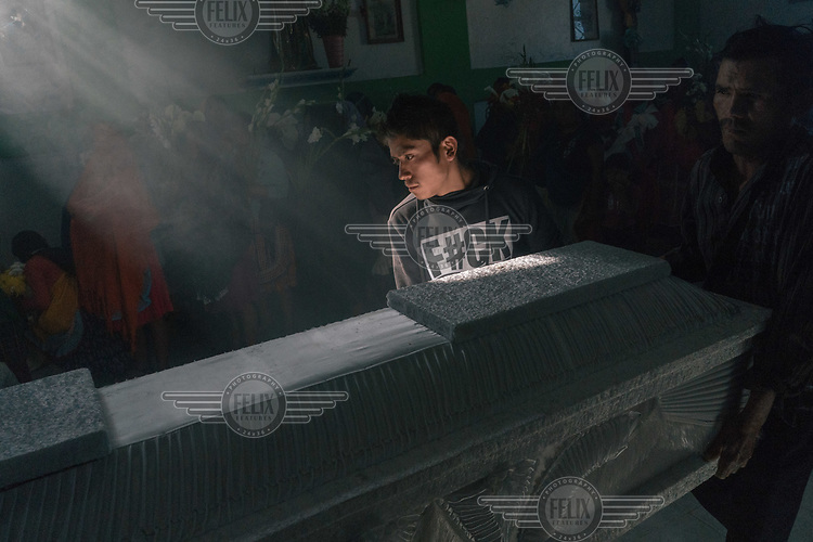 Ricardo Mendoza, a member of the Regional Coordinator of Community Authorities (CRAC-PF), helps to carry the coffin of his fifteen-year-old nephew, Israel Mendoza, at a church during the teenage boy's funeral. In December 2019, members of the Los Ardillos drug cartel brutally murdered 10 Nahuas indigenous musicians, including Israel, as they returned to Alcozacan after they had played at party outside the CRAC-PF defended territory.<br /><br />CRAC-PF was formed as a response by a cluster of remote farming villages, largely inhabited by indigeneous Nahuas indians, to the violent Los Adillos drug cartel who want to force the farmers to grow opium poppies. While elders admit that the training and arming of their children is really a ploy to get the attention of the central government who they say have failed to respond to their plight. Nonetheless, children cannot leave the villages defended by the CRAC-PF in order to attend secondary school and anyone caught by the brutal cartels is at risk of losing their life.