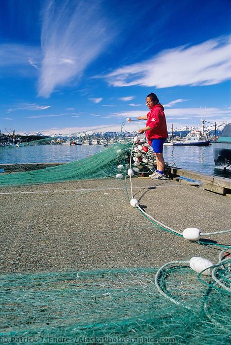 Commercial fisherwoman repairs drift net on harbor dock in the small coastal fishing community of Cordova, Prince William Sound, Alaska