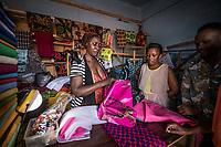 Uganda, Buikwe. WOW, solar system powering the television in Gertrude's home. Rose Senegenblo, Brenda Kanasiime, employees working in Gertrude's tailoring shop, using the solar lights.