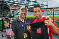 """9 June 2013: Sports photographer Ed Wolfstein (left) is presented with a gift from Washington Nationals Training Assistant John Hsu prior to a game against the Minnesota Twins at Nationals Park in Washington, DC. The Korean writing depicts """"Victory"""" which the Nationals accomplished by shutting out the Twins 7-0 in the first game of their Day-Night Double-Header. Mandatory Credit: Ed Wolfstein Photo *** RAW (NEF) Image File Available ***"""