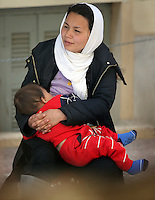 Pictured: 18 year old Afghan mother Zakia, breast-feeding Abulfaz in a street near Victoria Square Tuesday 08 March 2016<br /> Re: Migrants at Victoria Square, in central Athens, Greece.
