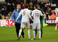 Pictured: Michu of Swansea (9) is held back by a stadium steward during what seems to be a verbal argument with Arsenal goalkeeper Lukasz Fabianski (in green).  Saturday 16 March 2013<br /> Re: Barclay's Premier League, Swansea City FC v Arsenal at the Liberty Stadium, south Wales.