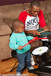 Two year old toddler boy watching father playing musiical instrument drums imitating him