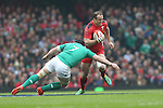 Ireland flanker Sean O'Brien tackles Wales centre Jamie Roberts.<br /> RBS 6 Nations<br /> Wales v Ireland<br /> Millennium Stadium<br /> 14.03.15<br /> ©Steve Pope - SPORTINGWALES