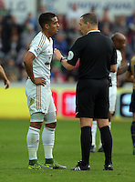 (L-R) Kyle Naughton of Swansea is spoken to by match referee KevinFriend during the Barclays Premier League match between Swansea City and Arsenal at the Liberty Stadium, Swansea on October 31st 2015
