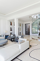 The impressive open-plan living space is of a classic contemporary design scheme, which emphasises pale muted colours and simple architectural forms.