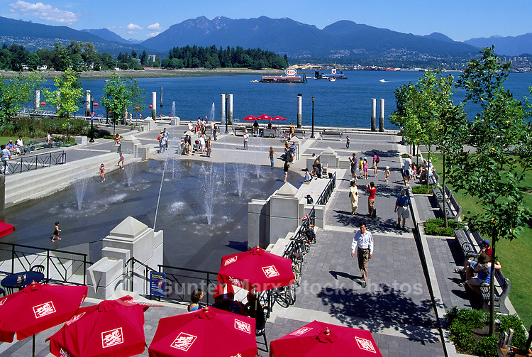 "Mill Marine Bistro - an Outdoor Restaurant Cafe with Red Sun Umbrellas, and Children playing at Water Park, along Waterfront at ""Coal Harbour"", in the ""West End"" of Vancouver, British Columbia, Canada, in Summer.  The North Shore Mountains (Coast Mountains) rise in the background."