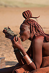 A Himba woman, with a traditional leather headress and ochre covered hair braids, lighting her pipe with a piece of fire wood. Himba women cover their bodies with a traditional mixture of ochre and butter fat giving their skin and hair a reddish coloration. Himba are nomadic herders of goats and cattle, living in the dry desert regions of northwestern Namibia and southern Angola. [NO MODEL RELEASE]