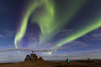 A photographer frames a man watching the aurora borealis on a rock outcrop,  as they swirl over the foothills surrounding Fairbanks, Alaska.