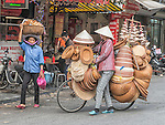 Women carrying or selling goods on the streets of Hanoi.