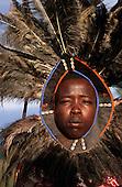 Lolgorian, Kenya. Siria Maasai Manyatta; 'lion head' moran with symbolic feather headdress with beads and cowrie shells.