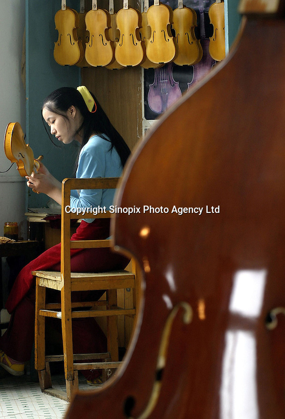 A Chinese craftswoman lacquers a violin at the Shanghai Wellsound-Tianyin Violin Factory  in Shanghai, China. Started in 1992 by a family with four generations of music instruments making experience, the company exports most of its high-end and hand crafted string instruments overseas. China supplies over 90% of the world's high-end music instruments..13-SEP-04