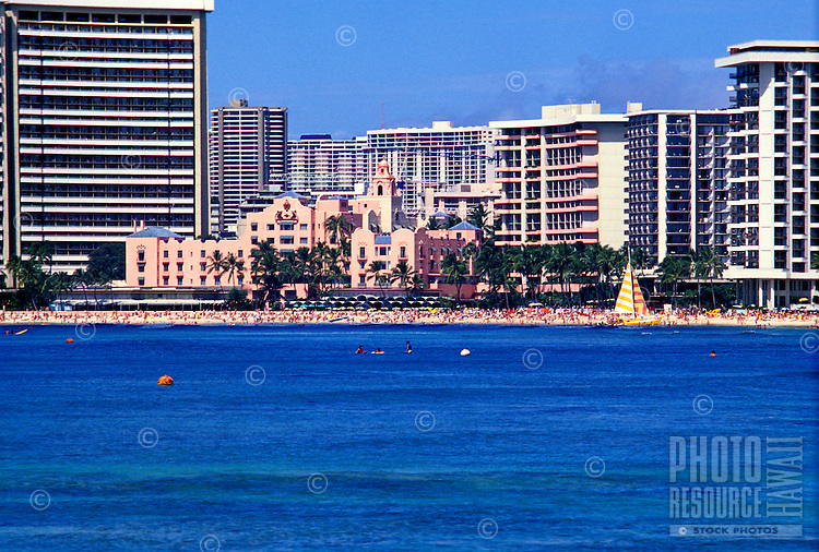 The historic Royal Hawaiian Hotel nestled among several newer hotels in Waikiki. Shot from the ocean showing the beach front.