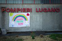 """Switzerland. Canton Ticino. Lugano. The firefighters have hanged a banner on the fire station's walls with the words: """"Everything will be better"""" and drawings of a rainbow, smiling sun and clouds, a heart and palms. Due to the spread of the coronavirus (also called Covid-19), the Federal Council has categorised the situation in the country as """"extraordinary"""". It has issued a recommendation to all citizens to stay at home, especially the sick and the elderly. The Federal Council (German: Bundesrat, French: Conseil fédéral, Italian: Consiglio federale, Romansh: Cussegl federal) is the seven-member executive council that constitutes the federal government of the Swiss Confederation. From March 16 the government ramped up its response to the widening pandemic, ordering the closure of bars, restaurants, sports facilities and cultural spaces. Only businesses providing essential goods to the population – such as grocery stores, bakeries and pharmacies – are to remain open. 18.03.2020 © 2020 Didier Ruef"""