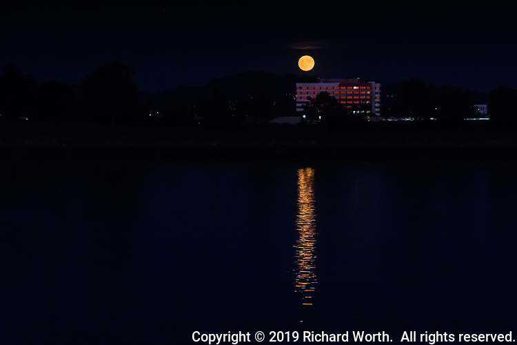 The Full Harvest Moon rises and reflects in the waters of the San Leandro Bay.  In between is an office building whose windows are reflecting the orange sunset glow.