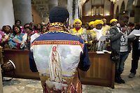 """Switzerland. Canton Valais. St-Maurice. Africa Saints Pilgrimage (Pèlerinage aux Saints d'Afrique). Religious <br /> ceremony in St-Maurice's abbey. African women and men gather for a catholic mass. A man wears a shirt with drawing of """"Our Lady of Fátima """" a title for the Virgin Mary due to her reputed apparitions to three shepherd children at Fátima, Portugal in 1917. The title of Our Lady of the Rosary is also sometimes used to refer to the same apparition. According to religious tradition, Mary was an Israelite Jewish woman and the mother of Jesus. Among her many other names and titles are the Virgin Mary or Blessed Virgin Mary, Mother of God, and Saint Mary in Western churches, Theotokos in Orthodox Christianity, and Maryam, mother of Isa in Islam. 2.06.13 © 2013 Didier Ruef"""