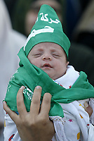"""A Palestinian child is wrapped in a green Islamic flag at a protest by the Islamic group Hamas against the upcoming U.S.-hosted Mideast peace conference, in Gaza City, Sunday, Nov. 25, 2007. Israeli, Palestinian, Arab and world leaders are set to meet in Annapolis, Maryland this week at a U.S. hosted peace conference..""""photo by Fady Adwan"""""""
