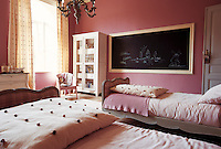 In this charming girl's bedroom the curtains are covered in pompoms matching the large cushions on each bed