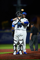High Point Rockers starting pitcher Bryce Hensley (34) hugs catcher Logan Moore (10) after being removed from the game against the Southern Maryland Blue Crabs at Truist Point on June 18, 2021, in High Point, North Carolina. (Brian Westerholt/Four Seam Images)
