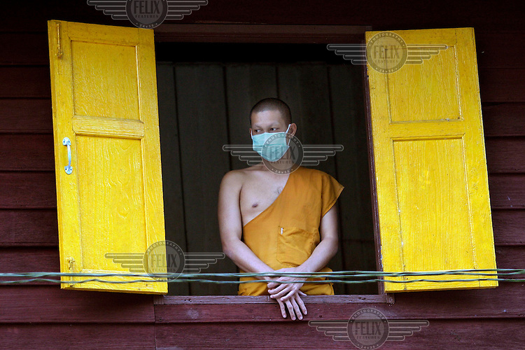 A Buddhist monk looks out over a pile of corpses of people killed in the tsunami which struck South Asia on 26/12/2004. Rescue workers attempted to gather and identify the bodies at various locations, mostly on temple grounds.An underwater earthquake measuring 9 on the Richter scale triggered a series of tidal waves which caused devastation when they struck dry land. 12 countries were affected by the tsunami, with a combined death toll of over 150,000. In Thailand many of the victims were Western tourists. © Fredrik Naumann