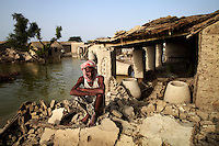 Surab Gadhi sits on the rubble of his destroyed home in Gulam village, Sindh province, Pakistan.
