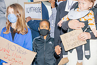 """People listen to children speak outside the Boston Police Department Headquarters during the """"Peaceful Children's March: Be the Change"""" demonstration in support of Black Lives Matter in Boston, Massachusetts, on Sun., June 7, 2020. The children's march was organized by siblings Naheem, 7, and Anaysha Benalfew, 10. The demonstration is part of a weeks-long nationwide response to the killing of George Floyd by Minneapolis police on May 25, 2020. The march started near the Nubian Square bus depot and continued to the nearby Boston Police Department headquarters, where marchers knelt for 8 minutes and 46 seconds, the time that police officers knelt on George Floyd's neck during his killing. A number of children, mostly people of color, then spoke about how people should be treated equally and how they wished they didn't have to grow up fearful that a police officer would kill them or their loved ones.  The signs here read """"Stop Killing Us,"""" """"I can't breathe,"""" """"No rest until there is Justice,"""" and """"Black Lives Matter."""""""