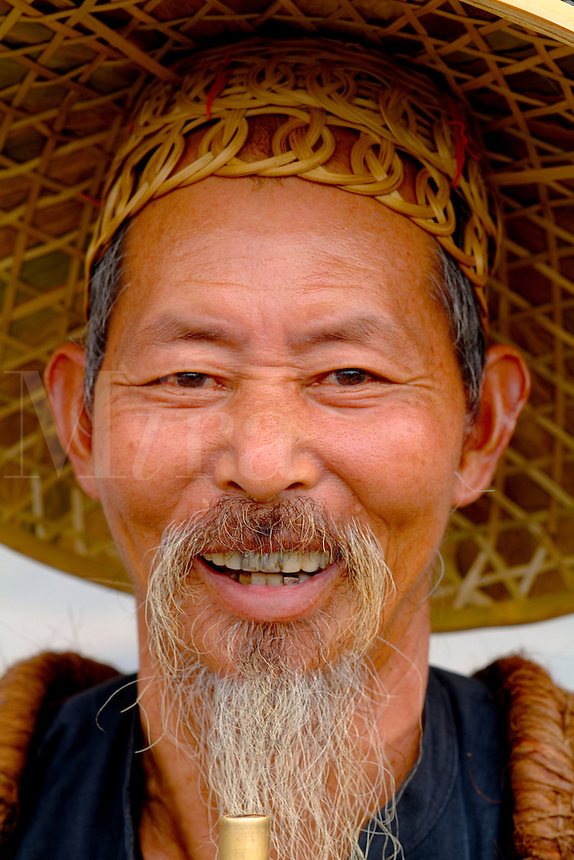 Old man fisherman portrait smoking in traditional costume in Yangshuo China