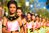 Beautiful Thai dancers in a line in traditional pink and green dresses during Loy Krathong festival in Sukhothai Historical Park, Thailand