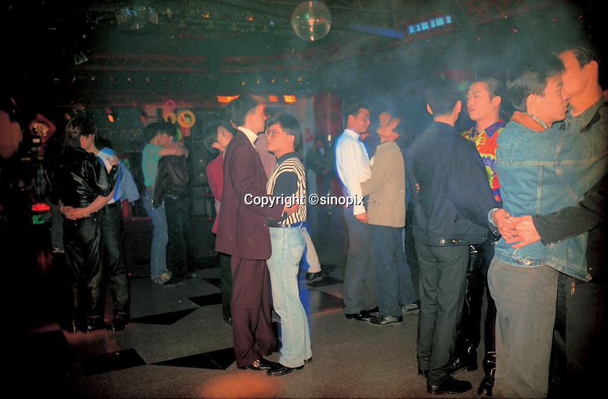 Gay men dance in a night club at Guangzou, China. .Homosexuality is still taboo in China but there are underground night club in most big cities.