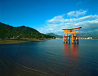 The bright red Sea-gate of Miyajima temple, Japan, against a background of sea and the low hills opf Miyajima island and the distant mainland of Japan