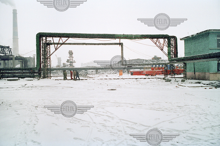 Industrial workers walking through the snow to work at a newly built coal-fired power station. China is in the process of building over 500 new coal power plants to meet the increasing energy demand.