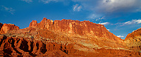9080010 panoramica view -  sunset light turns the sandstone formations of the waterpocket foldl red and gold in capitol reef national park in utah