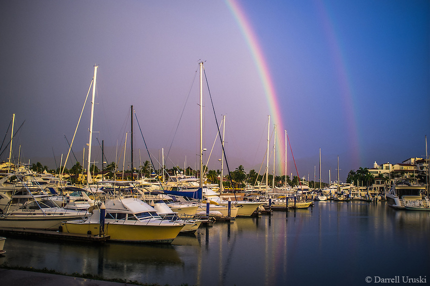 Fine Art Landscape Photograph of a double rainbow with water reflections in the ocean marina at Puerto Vallarta, Mexico.<br />