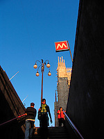 People on steps under Metro entrance sign and the Duomo, Milan, Ital