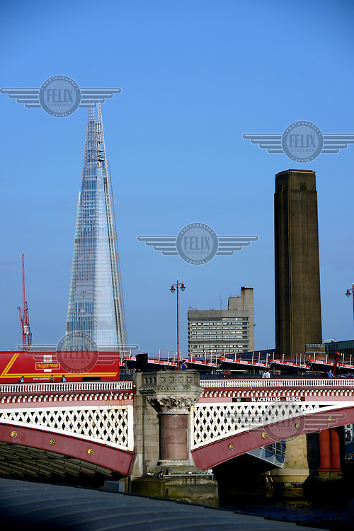 The Shard, at 310 metres is Western Europe's tallest building, looms behind Blackfriars Bridge, London. To the right is a brick chimney belonging to the Tate Modern art museum.