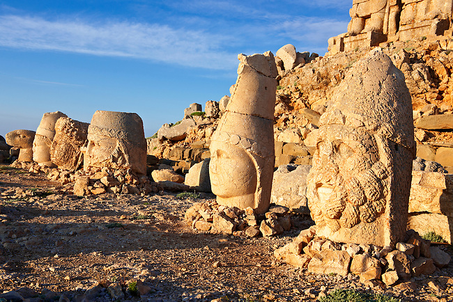Pictures & Images of the statues of around the tomb of Commagene King Antochus 1 on the top of Mount Nemrut, Turkey. Stock photos & Photo art prints. In 62 BC, King Antiochus I Theos of Commagene built on the mountain top a tomb-sanctuary flanked by huge statues (8–9 m/26–30 ft high) of himself, two lions, two eagles and various Greek, Armenian, and Iranian gods. The photos show the broken statues on the  2,134m (7,001ft)  mountain. 2