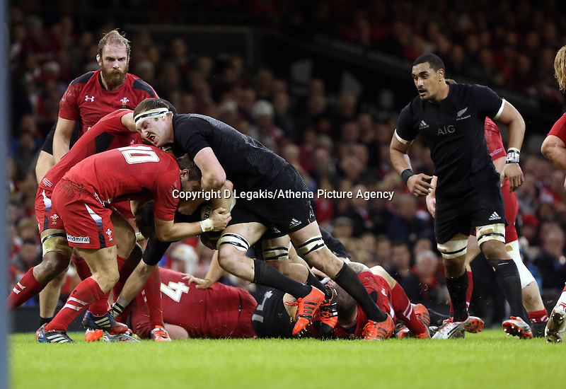 Pictured: Brodie Retallick of New Zealand (with ball) is brought down by Dan Biggar of Wales Saturday 22 November 2014<br /> Re: Dove Men Series 2014 rugby, Wales v New Zealand at the Millennium Stadium, Cardiff, south Wales, UK.