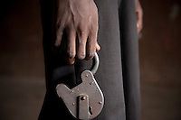 An inmate in Pademba Central Prison holds a padlock used in cells housing prisoners with mental health issues.